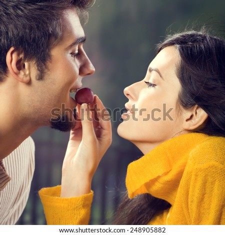 Portrait of young couple eating grapes, outdoor - stock photo