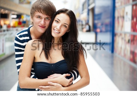 Portrait of young couple embracing at shopping mall and looking at camera. Horizontal shot - stock photo