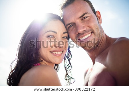 Portrait of young couple embracing each other on the beach on a sunny day