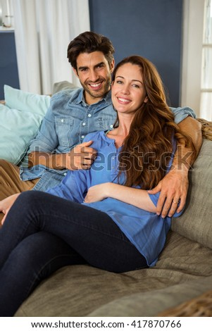 Portrait of young couple embracing in living room - stock photo