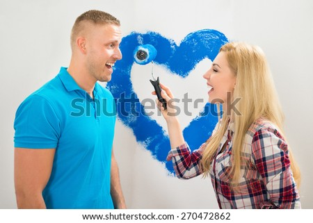 Portrait Of Young Couple Having Fun While Painting In New House - stock photo