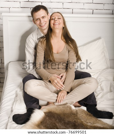 portrait of young couple in bed hugging - stock photo