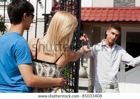 Portrait of young couple in front of one-family house in modern residential area. Agent giving keys to woman and welcoming family to their new home