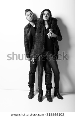 Portrait of young couple in love posing at studio. Fashion photo. - stock photo