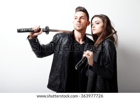Portrait of young couple in love posing with samurai swords. Fashion photo - stock photo