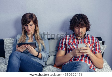 Portrait of young couple in love using electronic devices while resting over a bed. Leisure time at home concept. - stock photo