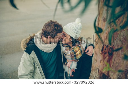 Portrait of young couple in love with hat and scarf embracing and kissing under a tree in a cold autumn day. Love and couple relationships concept. - stock photo