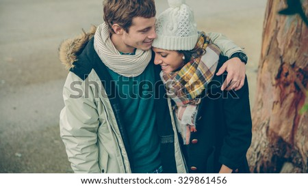 Portrait of young couple in love with hat and scarf embracing and laughing in a cold autumn day. Love and couple relationships concept. - stock photo