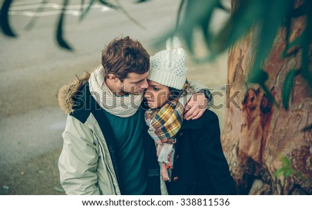 Portrait of young couple in love with hat and scarf embracing under a tree in a cold autumn day. Love and couple relationships concept. - stock photo