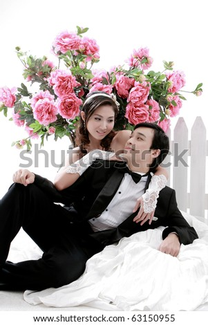 Portrait of young couple in lovely action with flower in background - stock photo