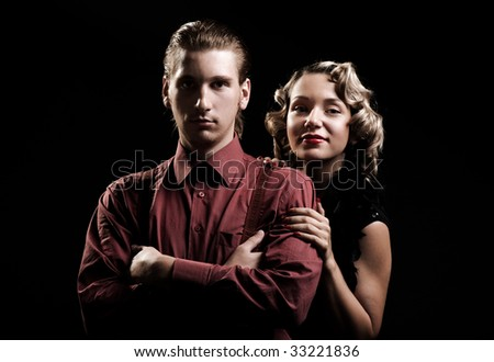 portrait of young couple in retro style against black background - stock photo