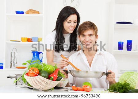 portrait of young couple in their kitchen happy smile, looking at camera, - stock photo