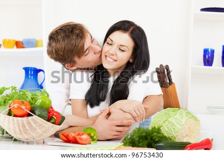 portrait of young couple in their kitchen kiss, hug, embracing happy smile, looking at camera, man kissing woman cheek - stock photo