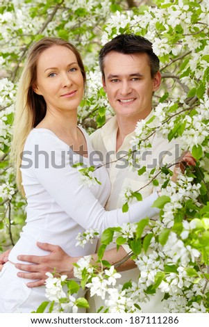 Portrait of young couple looking at camera between blooming apple-trees - stock photo