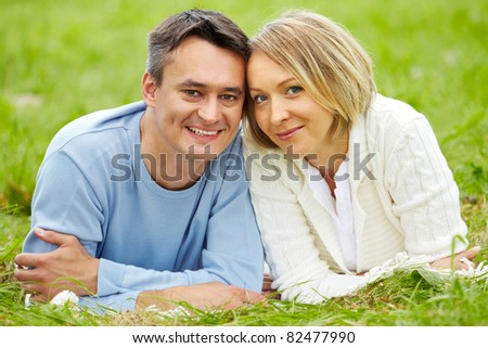 Portrait of young couple looking at camera while having rest in park - stock photo