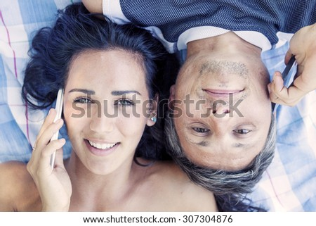 portrait of young couple lying on cloth talking phone - stock photo
