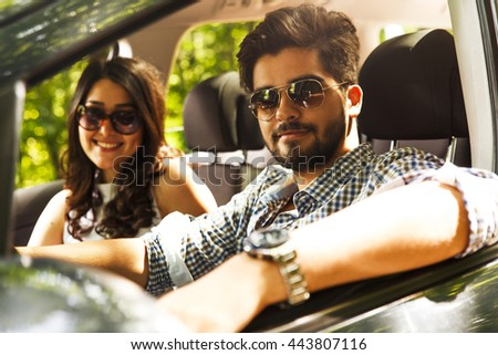Portrait of young couple sitting in car.