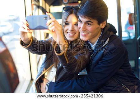 Portrait of young couple taking selfies with smartphone at bus. - stock photo