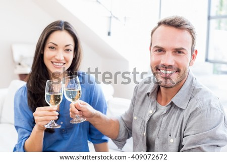 Portrait of young couple toasting wine glasses at home - stock photo