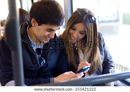 Portrait of young couple using mobile phone at bus. - stock photo