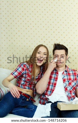 Portrait of young couple watching TV and expressing their emotions - stock photo