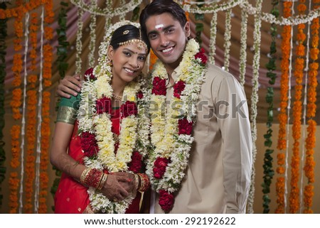 Portrait of young couple wearing garlands during traditional Indian wedding - stock photo