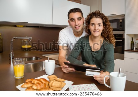 Portrait of young couple with electronic tablet and credit card buying on internet. Online shopping concept. - stock photo