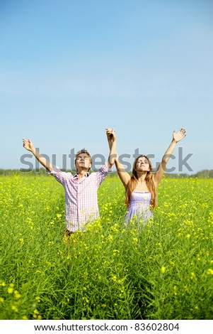 Portrait of young couple with raised arms standing in flower field - stock photo