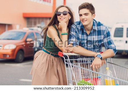 portrait of young couple with shopping cart outdoors - stock photo