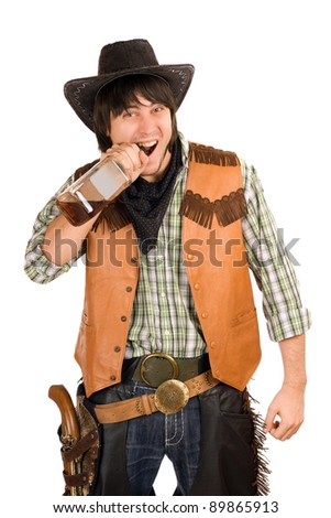 Portrait of young cowboy with a bottle of whiskey - stock photo