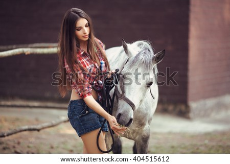 Portrait of young cowgirl feeding white horse outdoors