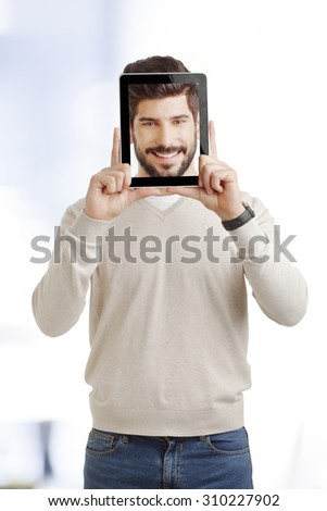 Portrait of young creative man standing at office and holding digital tablet before his face. Smiling businessman face appears on screen. - stock photo