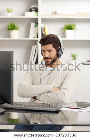 Portrait of young creative sitting at desk in front of computer with headphone and working at office.