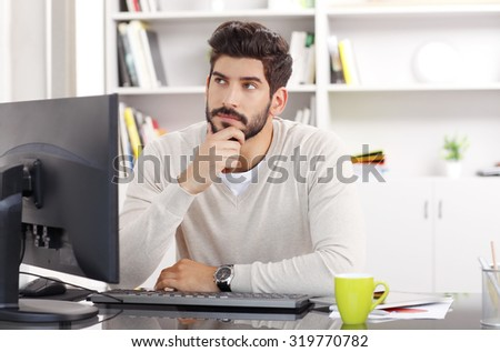 Portrait of young creative sitting at office and working while he thinks the solution of the problem. - stock photo