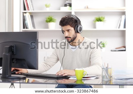 Portrait of young creative with headphone sitting in front of computer at office and listening music online.