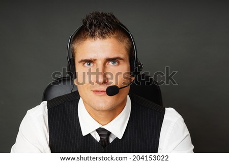 Portrait of young customer service operator on gray background