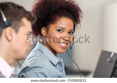 Portrait of young customer service representative with male colleague working in office
