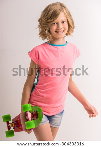Portrait of young cute girl holding skateboard in studio against white background. - stock photo