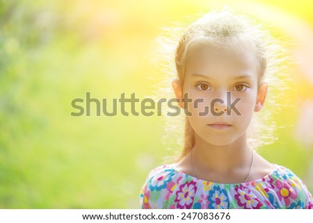portrait of young cute girl in dress, against background of summer green park - stock photo