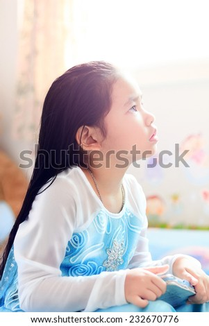 Portrait of young cute girl in princess fairy clothes looking up something on top - stock photo