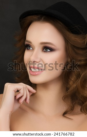 Portrait of young cute smiling woman wearing black hat over dark background - stock photo