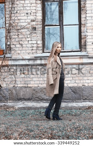 Portrait of young cute woman in autumn coat on the background of houses. Fashion photo. Hair of girl is blowing in the wind - stock photo