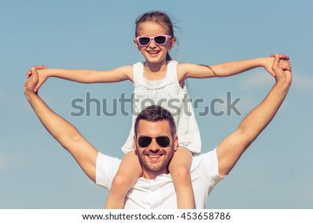 Portrait of young dad and his cute little daughter looking at camera and smiling. Girl is sitting on her father's shoulders, sky on the background - stock photo