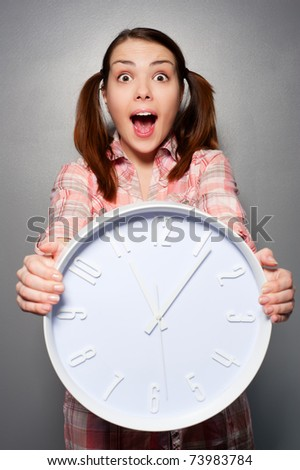 portrait of young disturbed woman holding wall clock - stock photo
