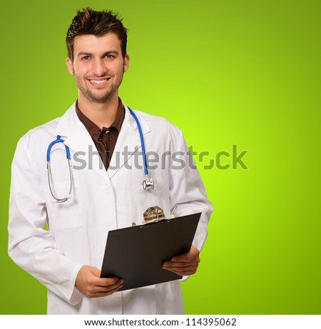 Portrait Of Young Doctor Isolated On Green Background - stock photo