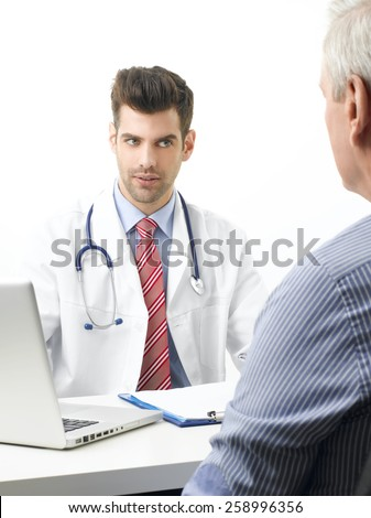 Portrait of young doctor sitting at desk with elderly patient while check up and write diagnosis. Isolated on white background. - stock photo
