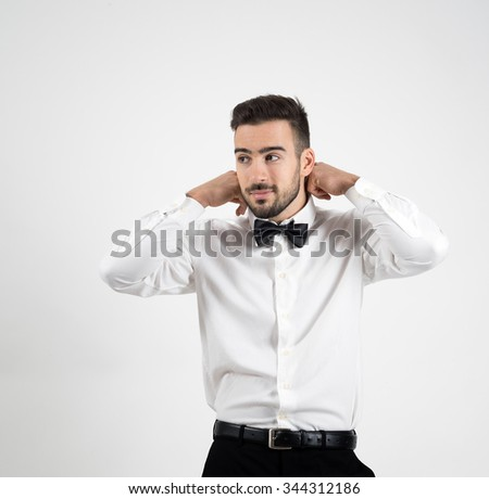 Portrait of young elegant luxurious man adjusting bow tie looking away over grey studio background.