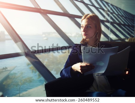 Portrait of young elegant woman sitting in modern office interior holding papers and pensively gazing out of the window, filtered image with flare sun light from the window - stock photo