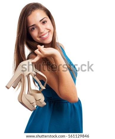 portrait of young elegant woman wearing a blue dress and holding a high heeled shoes - stock photo