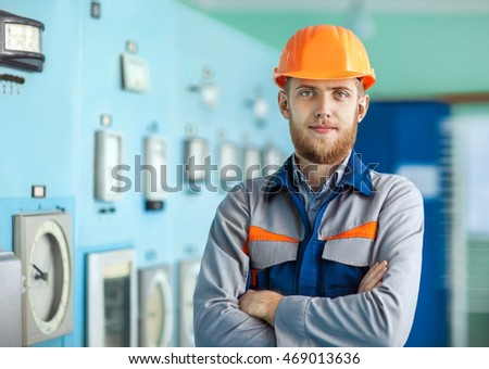 Portrait of young engineer at control room in factory. Crossed arms
